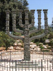 Отлитое из бронзы пятиметровое скульптурное изображение меноры, установлено напротив входа в здание Кнессета в Иерусалиме. Автор - английский скульптор Бенно Элкана (1877-1960).