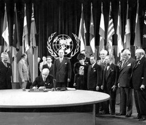 26 июня 1945 года, Госсекретарь Стеттиниус подписывает Хартию ООН. За его спиной — Вирджиния Гилдерслив. Слева — Президент Трумэн